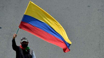 La voltean simbólicamente para expresar la sangre derramada en las protestas en Colombia. Foto: AFP
